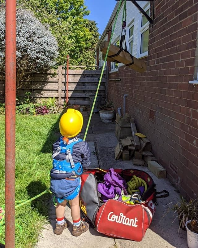Young child learning Tree Surgeon & Arborist techniques, called rigging, that will assist in tree removal in confined spaces.