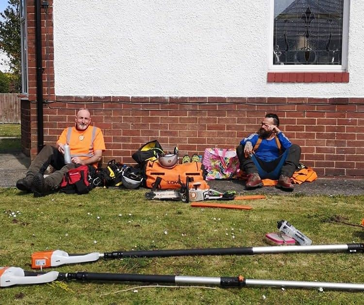 Tree surgeons sitting having a tea break following a tree removal and a crown reduction.